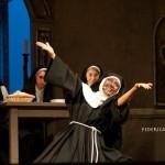 Foto tratta dallo spettacolo I Will Follow Him. Una suora canta e balla sorridente con le braccia aperte mentre due suore in fondo guardano incuriosite.